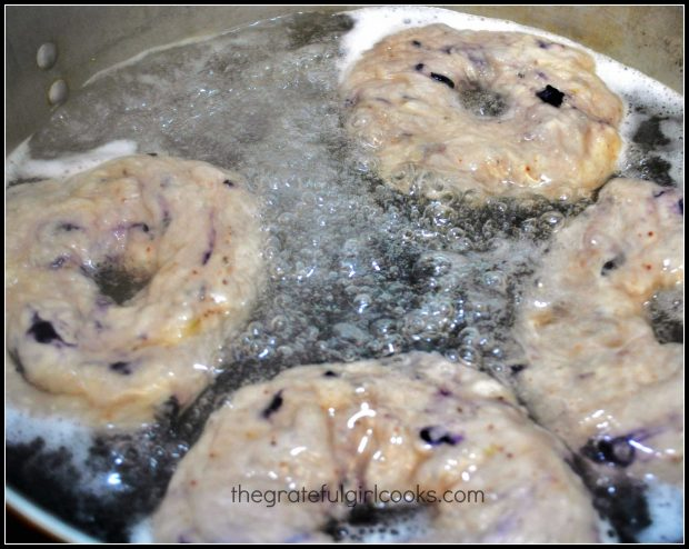 Blueberry bagels cooking in boiling water in pan