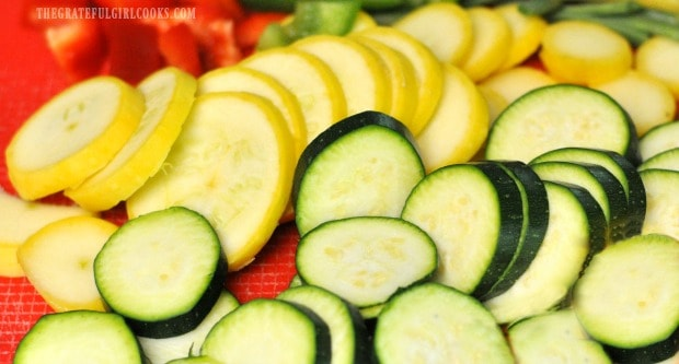 Zucchini squash and bell peppers, sliced for honey lime chicken skewers.