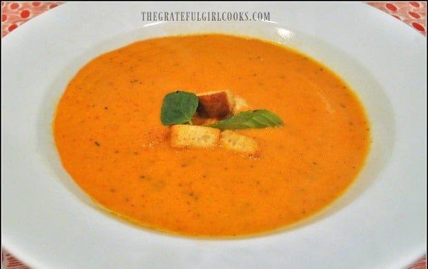Creamy tomato basil soup is served in white bowl, with croutons and basil leaves as garnish.