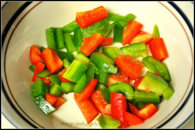 Red and green bell peppers are chopped for Hawaiian meatballs and rice.