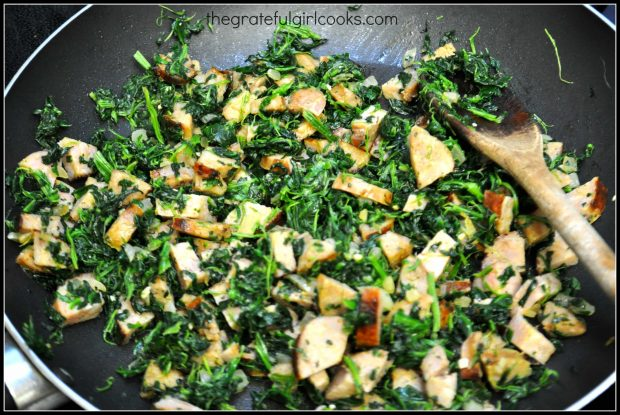 Spinach and garlic are added to the skillet of sausage and onions.