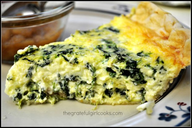 A side view of a slice of Italian sausage spinach quiche on a plate.