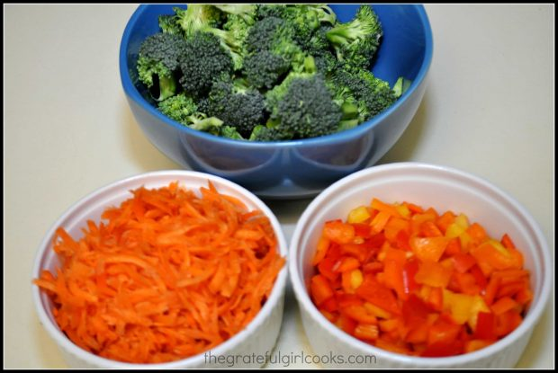 Broccoli, bell peppers and carrots are chopped and prepped before stir frying.
