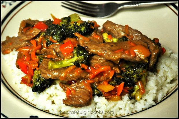 Orange Beef Stir Fry is served on top of white steamed rice.
