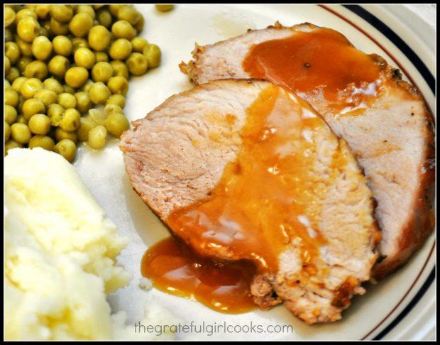 Mashed potatoes and peas are served with orange glazed pork roast.