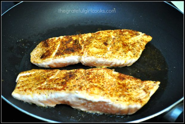 Pan seared creole salmon cooking in skillet.
