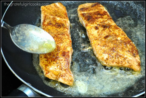 Salmon, seasoned with Cajun seasoning, cooking in a skillet.