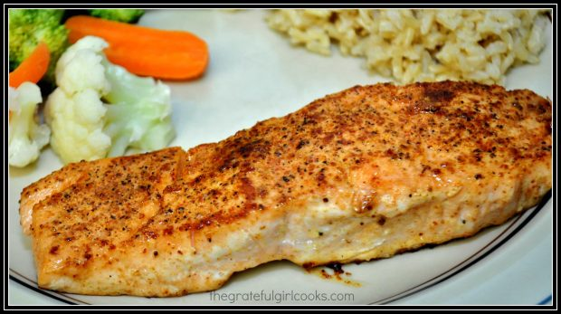 A pan seared creole salmon fillet is served with rice and vegetables on the side.