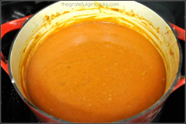 Homemade red sauce for shredded pork smothered burritos is complete after adding tomato paste and sauce to pan.
