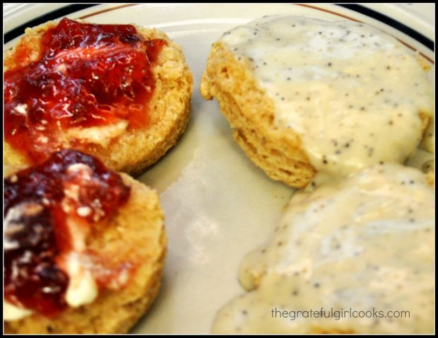 Biscuits topped with gravy, and other biscuits (on the left) topped with jam.