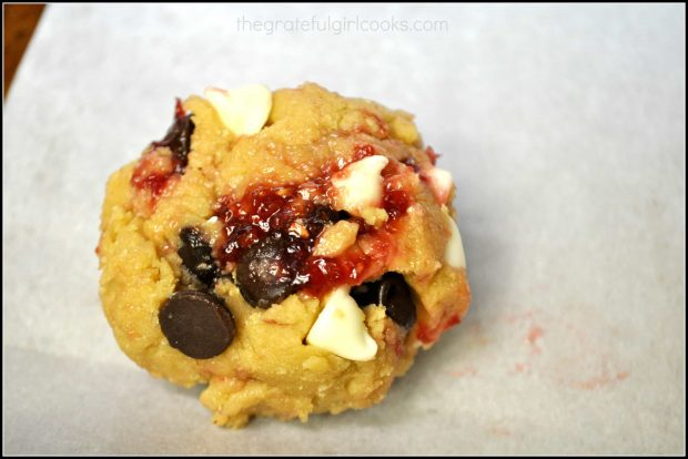 A close up view of a cookie (before baking), with raspberry jam and chocolate chips showing.