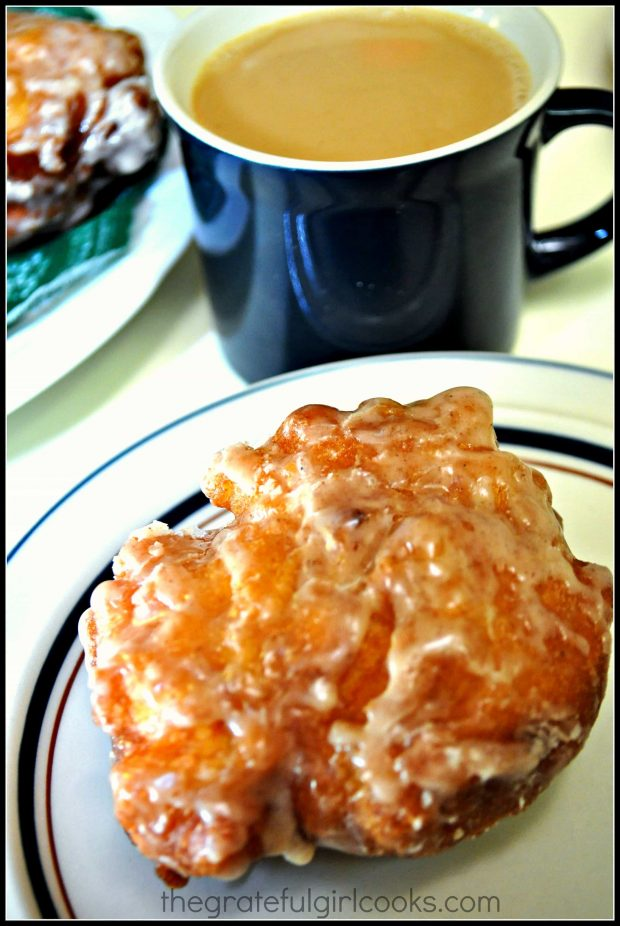 Cup of coffee with one apple fritter on a plate