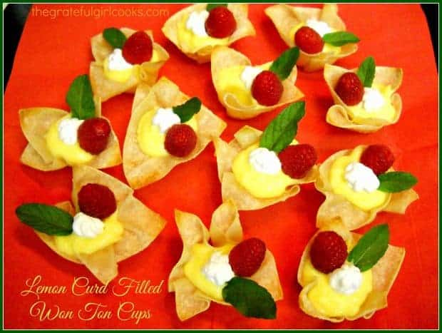 These tasty dessert bites, featuring filled lemon curd won ton cups, garnished with whipped cream, mint and a raspberry, will be a big hit!
