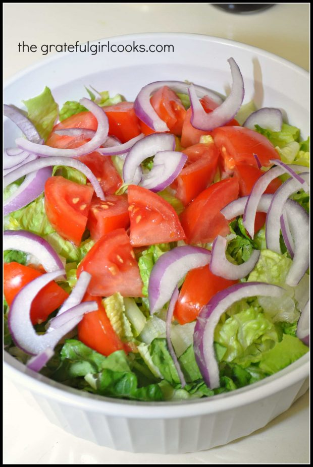 Romaine lettuce, red onion slices and tomatoes go into the Greek salad.