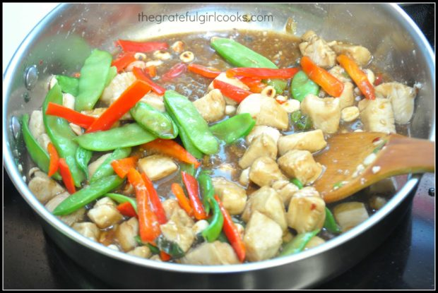 Veggies, sauce, and dry roasted nuts are added to healthy kung pao chicken in skillet.