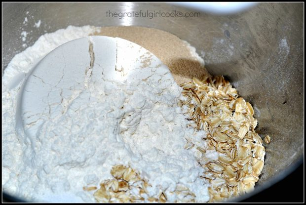 Oats, flour and other bread ingredients in metal mixing bowl