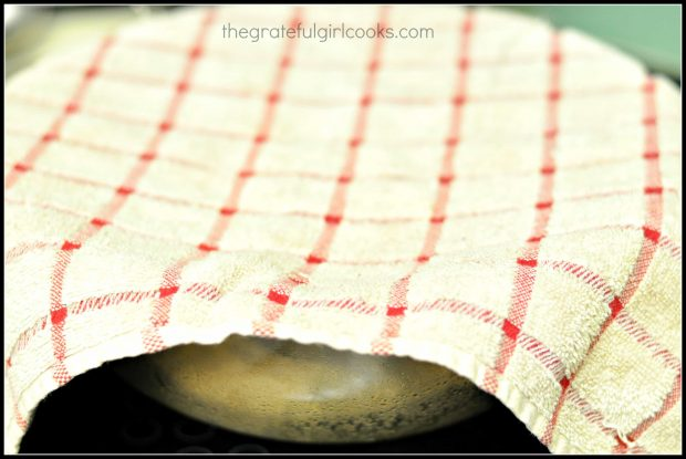 Dough rising in glass bowl with dish towel on top