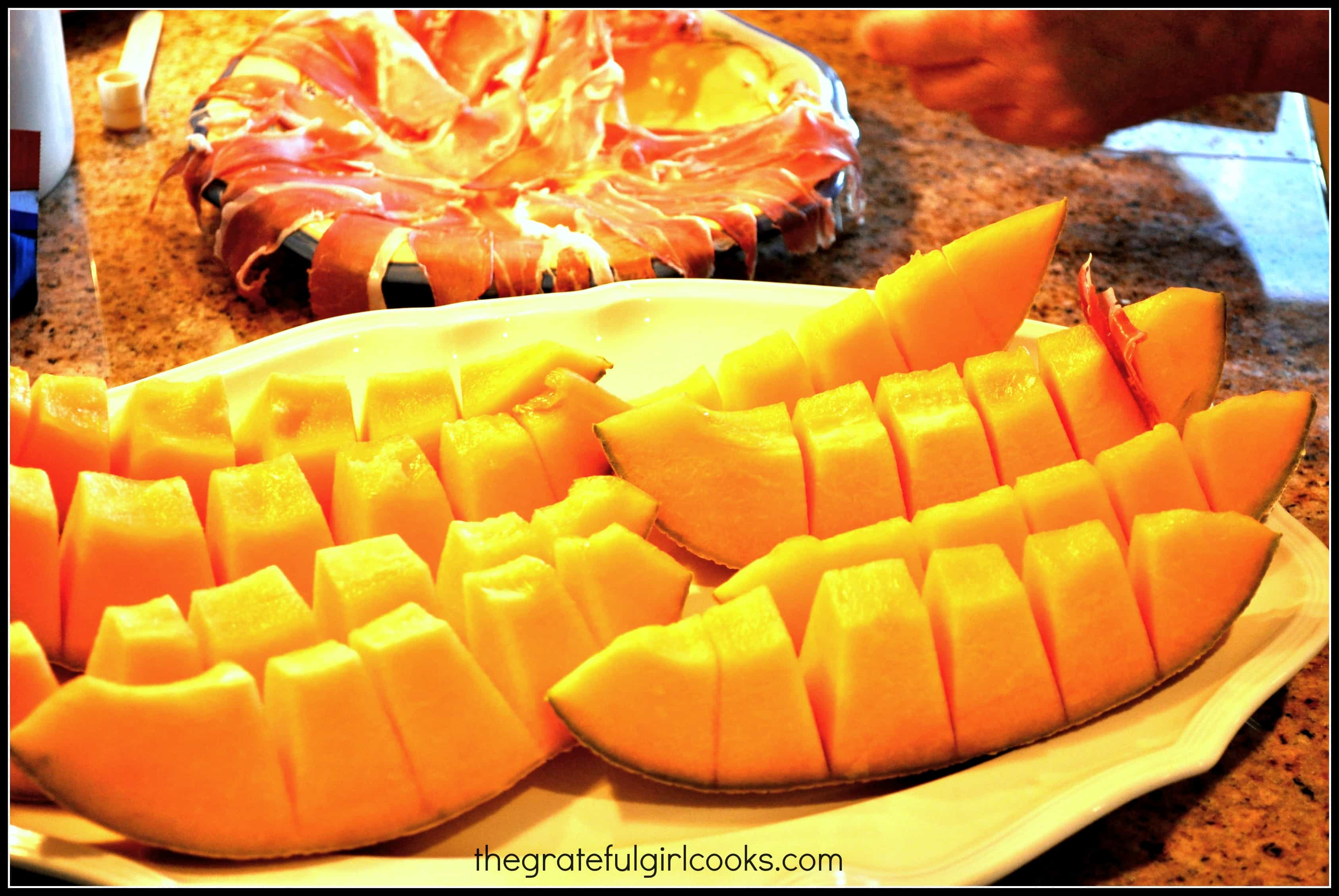 Cantaloupe cut into slices, with prosciutto slices in background