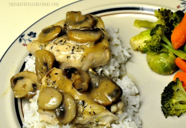 Chicken Marsala is served on a bed of rice, with mixed vegetables on the side.