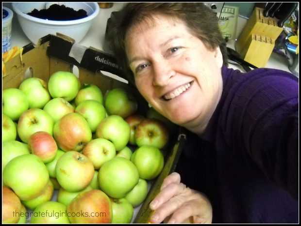 Woman smiling with a box of apples.