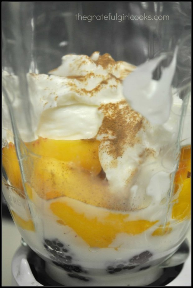 Almond milk and yogurt added to peaches and berries in blender