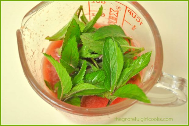 Fresh mint leaves are added to a small amount of watermelon puree