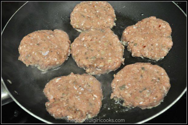 6 breakfast sausage patties cooking in skillet