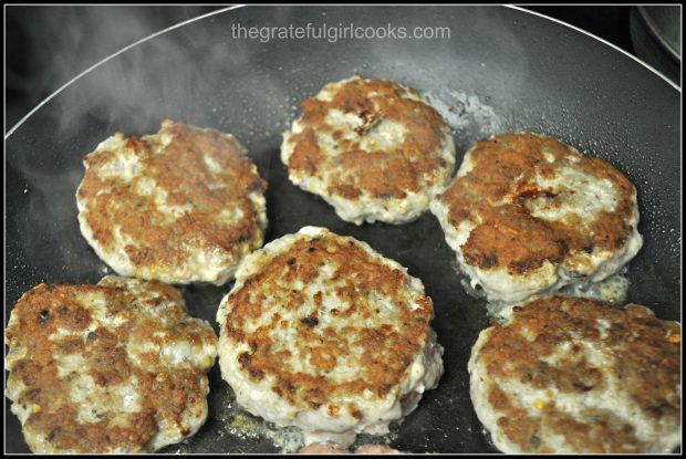 Browned homemade sausage patteis cooking in skillet