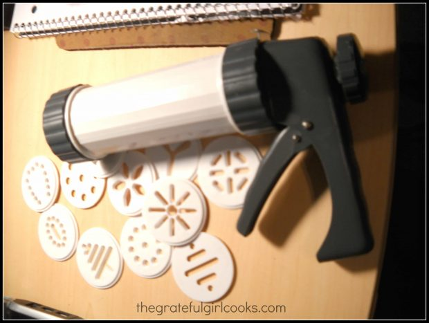 A cookie press is used to make holiday spritz cookies.