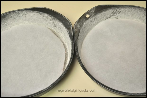 Two cake pans are dusted with flour, and parchment paper is placed on bottom.
