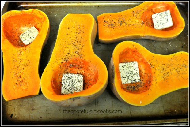 Butternut squash are halved, seeded, and butter, salt and pepper added before baking.