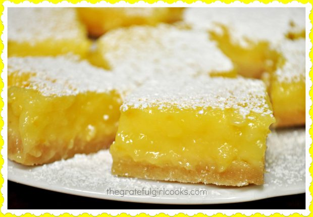 Close up photo of lemon bars on a white plate.