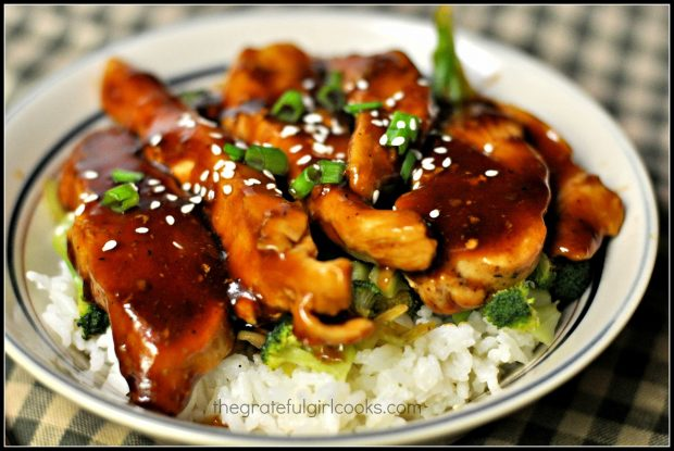 Teriyaki chicken rice bowl is topped with chicken, glaze, green onions and sesame seeds before serving.