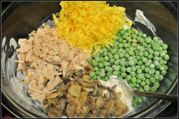 Tuna, mushrooms, cheddar cheese and peas are added to sauce for tuna noodle casserole.