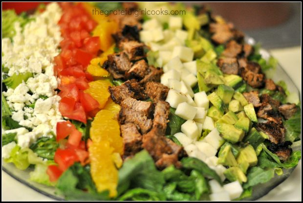 Ingredients for Southwestern cobb salad are placed in rows on Romaine lettuce before serving.