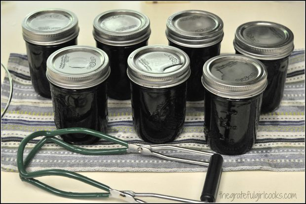 Jars of blueberry jam are sealed and cooling down on dish towel