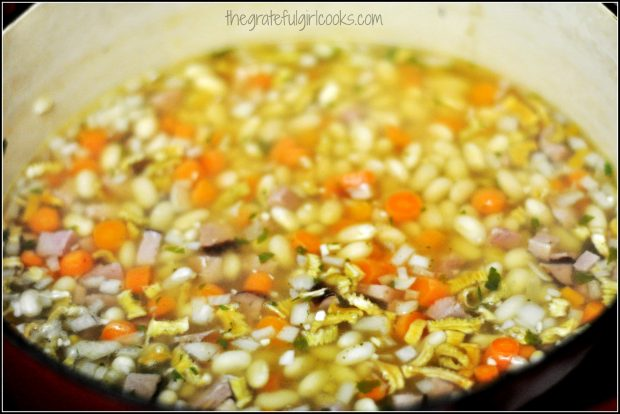 Beans, ham, carrots, celery and onion for soup, cooking in pan
