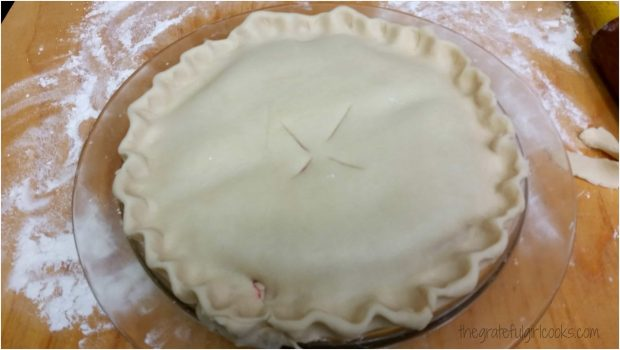 A top crust is placed on top of melba pie filling, and edges of crust are crimped.