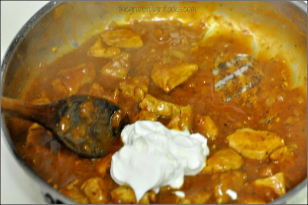 Sour cream added to pork and sauce in skillet