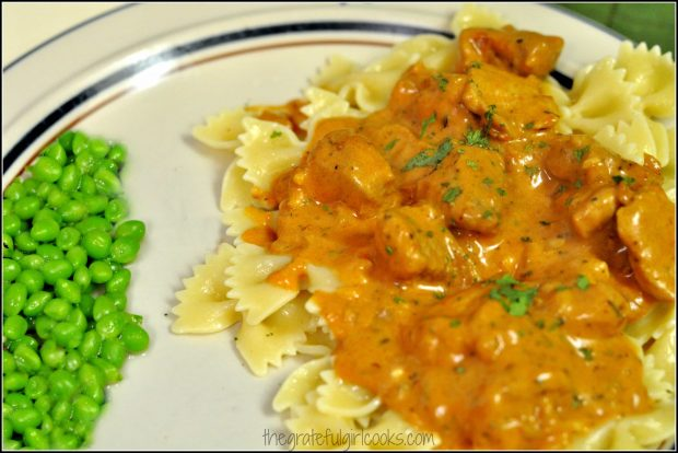 Pork paprikash and noodles on a plate with peas