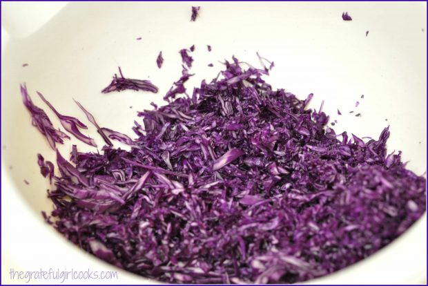 Shredded purple cabbage in bowl.