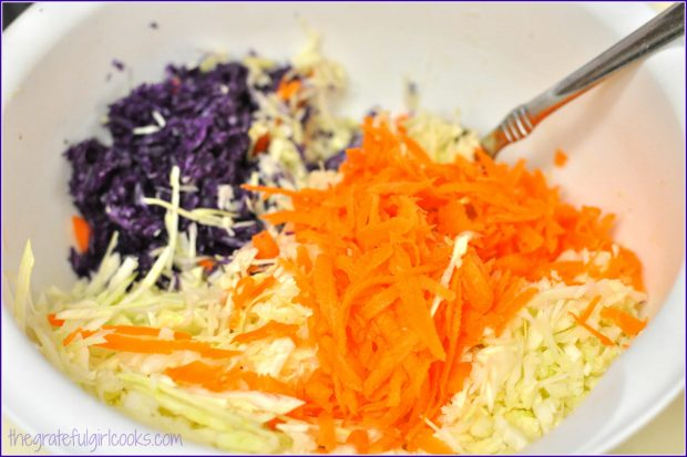 Grated purple and green cabbage, plus carrots in bowl.