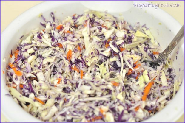 Green and purple cabbage, plus carrot shreds are mixed together in large bowl.