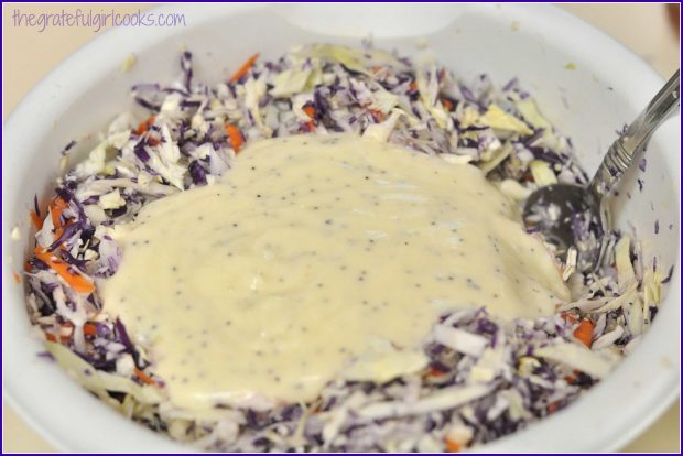 A poppyseed dressing is added to the purple coleslaw, and mixed in.