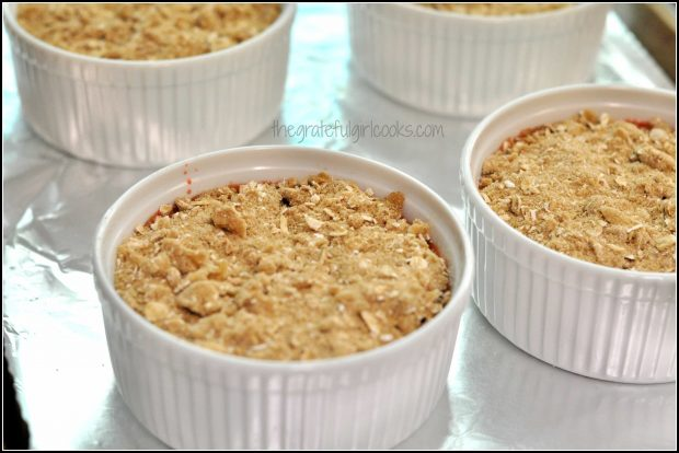 Crumb topping on top of strawberry cobbler ramekins.