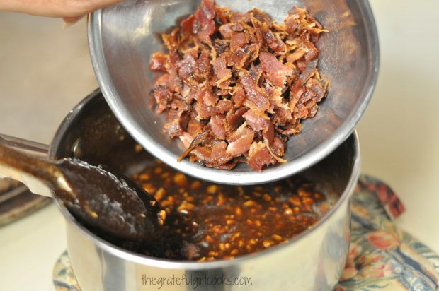 Crumbled, cooked bacon pieces are added to praline mixture in pan.