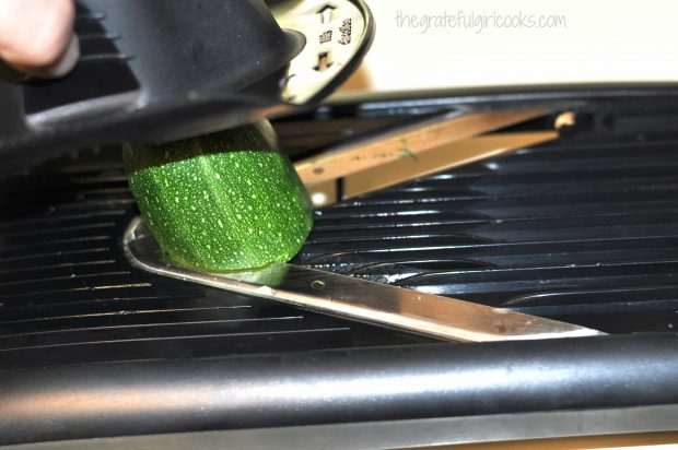 Slicing zucchini for salad very thinly using a mandolin