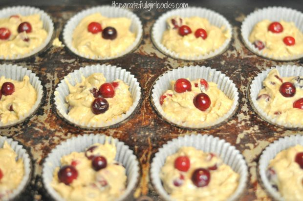 Cranberry orange muffins batter is placed into paper liners in pan before baking.