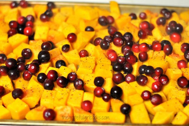 Fresh cranberries are added to roasted butternut squash, then placed back into oven.