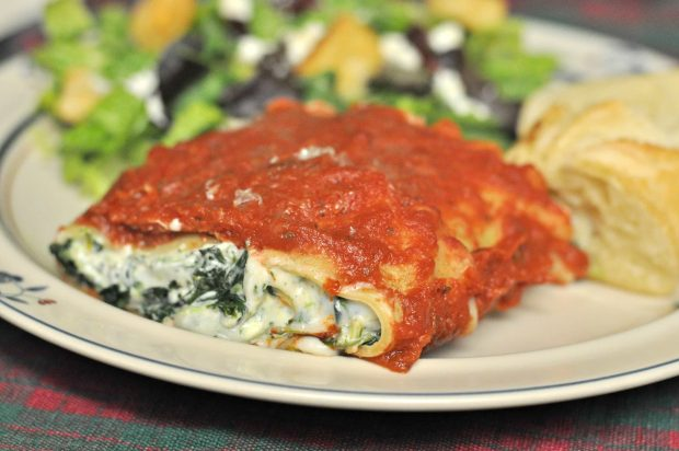 Florentine lasagna roll is served with salad and bread, on plate